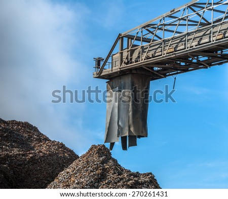 A conveyor machine with dumped scrap metal mounds. - stock photo
