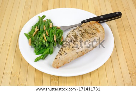 A cooked chicken breast with green beans and sliced almonds on a white plate with fork atop a wood place mat. - stock photo