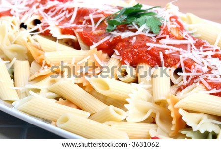 a cooked plate of macaroni with bolognese sauce sprinkled with grated cheese.