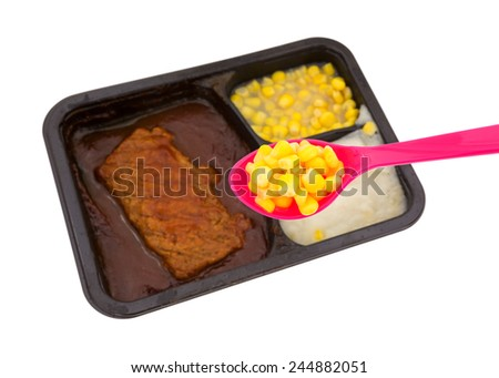 A cooked TV dinner in the background with corn on spoon in the foreground on a white background. - stock photo