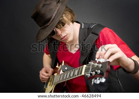 A cool looking guitar player tuning his instrument - stock photo