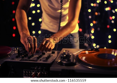 a cool male dj on the turntables - stock photo