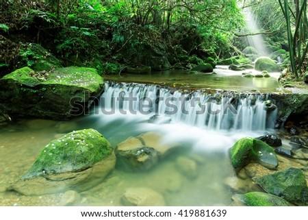 A cool refreshing waterfall hidden in a mysterious forest of lush greenery with sunlight shining through green leaves ~ Beautiful river scenery of Taiwan in springtime - stock photo
