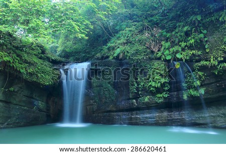 A cool refreshing waterfall in a mysterious forest of lush greenery ~ Scenery of Taiwan - stock photo