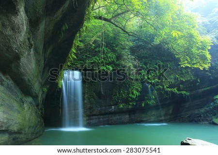 A cool refreshing waterfall into an emerald pond hidden in a mysterious forest of lush greenery ~ Scenery of Taiwan   - stock photo
