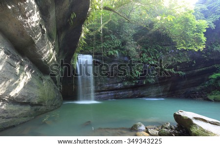 A cool refreshing waterfall into an emerald pond hidden in a mysterious forest of lush greenery ~ Beautiful river scenery of Taiwan in springtime ( Natural light version)  - stock photo