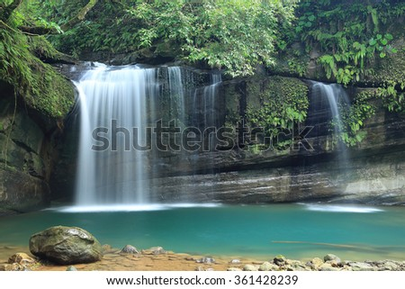 A cool refreshing waterfall pouring into an emerald pond hidden in a mysterious forest of lush greenery ~ Beautiful river scenery of Taiwan in spring - stock photo