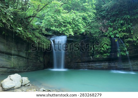 A cool refreshing waterfall pouring into an emerald pond in a mysterious forest of lush greenery ~ Beautiful river scenery of Taiwan in springtime - stock photo