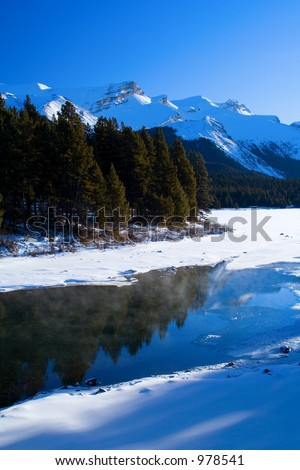 A cool scene mountain scene featuring open water in mid winter.