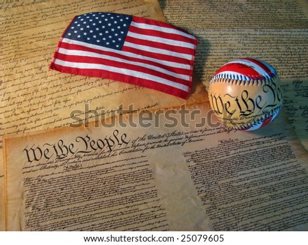 A copy of the Constitution of the United States accompanied by a flag and a baseball with the words of the Constitution on it. - stock photo