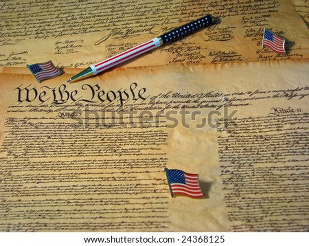 A copy of the Constitution of the United States resting on a copy of the Declaration of Independence accompanied by flags and a flag pen. - stock photo