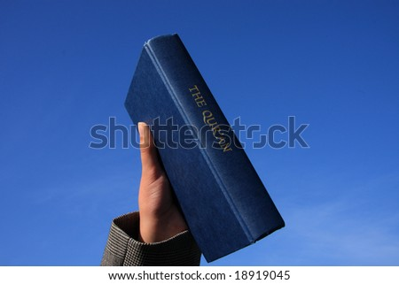 A copy of the Koran held up against blue sky background - stock photo