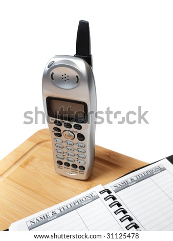 A cordless phone on a cutting board, with a blank name and telephone directory, isolated on white.