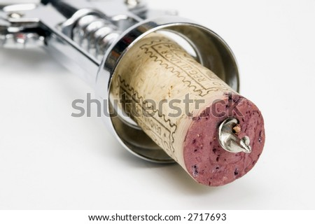 A corkscrew piercing a red wine cork on a white background - stock photo