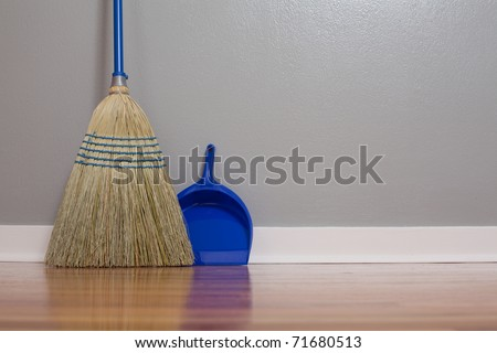 A Corn Broom on New Hardwood Flooring with a dust pan - stock photo