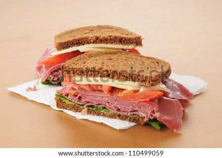 A corned beef and swiss cheese sandwich on a napkin - stock photo