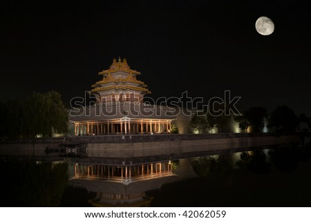 A corner of The Forbidden City, which is in Beijing China, reflected in the water, at night and with full moon.