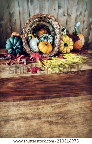 A cornucopia with squash, gourds, pumpkins, wheat and leaves on an old antique harvest  table.  Room for copy space. Filtered for an vintage retro look.  - stock photo
