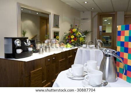 A corporate coffee area with tables, coffee pots and cups.