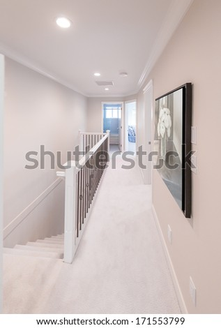 A corridor on the upper level of a house with the stairs and the rooms at the end. Interior design.