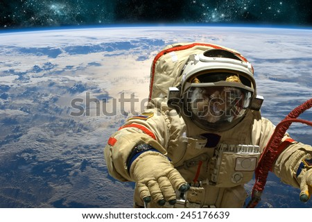A cosmonaut floats in space above Earth. Stars shine in the background. Elements of this image furnished by NASA. - stock photo