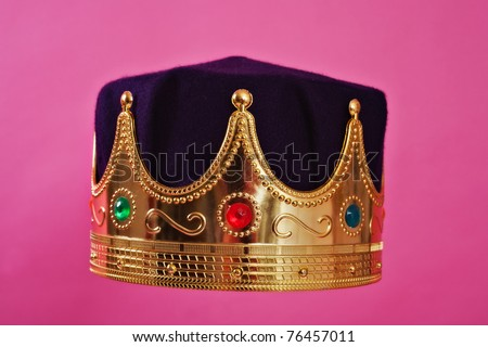 a costume prop of a queen's crown on a pink background