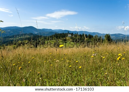 A cottage on the hill with surrounded by mountains and meadows - stock photo