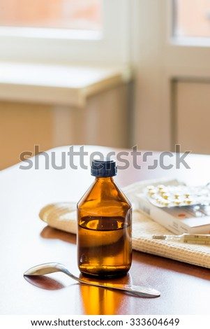 A cough syrup bottle with a spoon, a thermometer and some pills blister on the table close to the window - stock photo