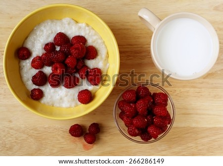 A country breakfast with pile of ripe raspberries, glass of milk and porridge - stock photo