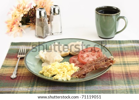A country breakfast with scrambled eggs, crispy bacon, biscuits and gravy, sliced tomatoes and hot coffee - stock photo