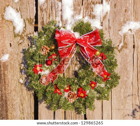 A country Christmas wreath on old barn - stock photo