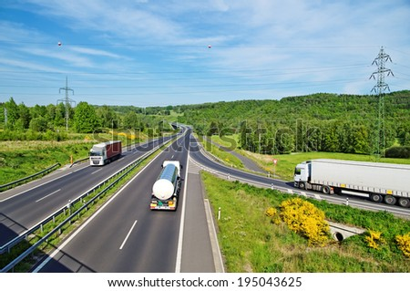 A country landscape with a highway, the highway goes truck and a tank truck, from the entrance to the highway coming white truck, in the distance electronic toll gate,  top view - stock photo