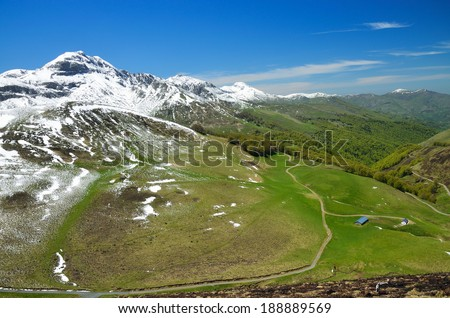 A country road is twisting on the green slope covered with snow in the spring mountains Pyrenees. - stock photo