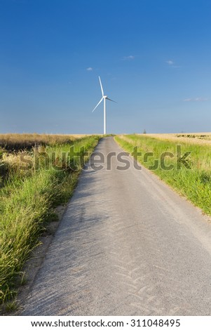 A country road leadings towards a wind turbine in the Eifel, Germany.