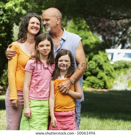 A couple affectionately stand with their two young daughters in their front yard. Square shot. - stock photo