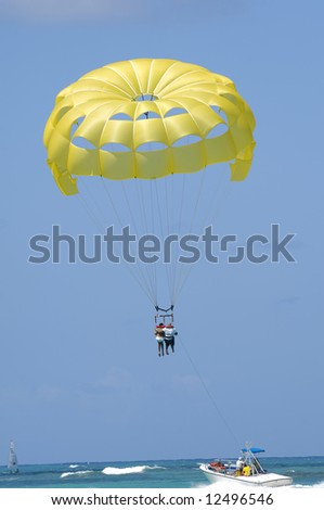 A couple are parasailing over the caribbean sea. The Dominican Republic, Punta Cana. - stock photo