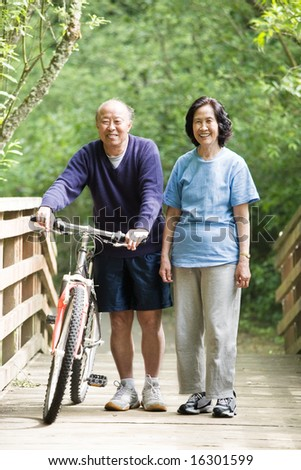 A couple asian mature talking while walking and exercising at a park - stock photo