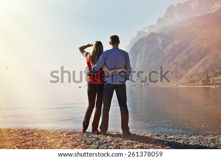 A couple at a mountain lake - stock photo