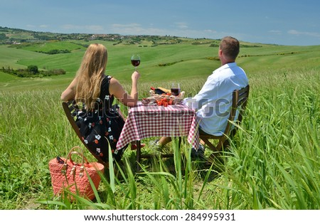 A couple at the table in the middle of a Tuscan field. Italy - stock photo
