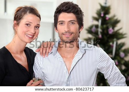 a couple behind a Christmas tree inside an apartment - stock photo