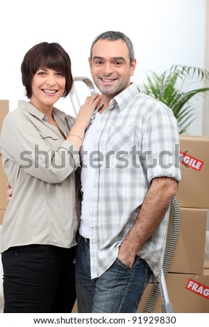 a couple behind  a pile of cartons inside a house - stock photo