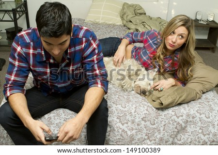 A couple being talking in the bedroom with a dog.  - stock photo