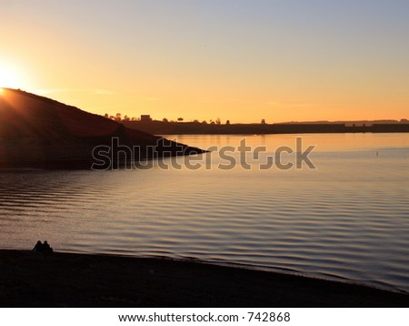 A couple by the lake at sunset - stock photo