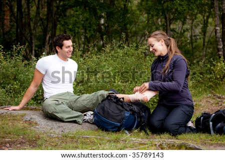 A couple camping and putting on a leg bandage - stock photo