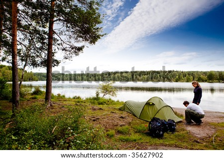 A couple camping on a lake landscape - stock photo