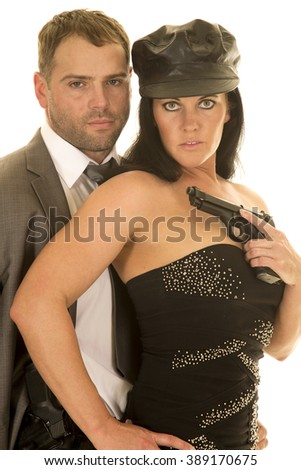 A couple close together, she has a pistol in her hand. - stock photo