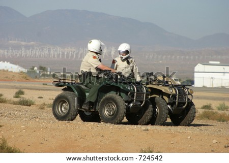 A couple cops patrol a desert airport on their ATV's. - stock photo