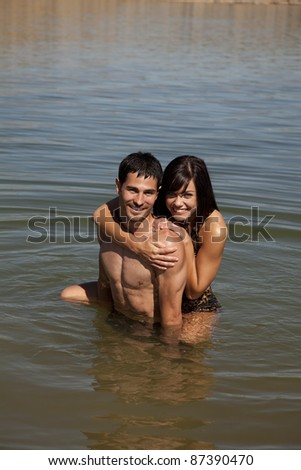 A couple cuddling in the water with smiles on their faces. - stock photo