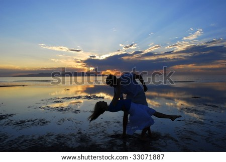 A couple dancing on a beach during an amazing sunset - stock photo