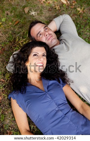 A couple day dreaming while laying on grass - stock photo